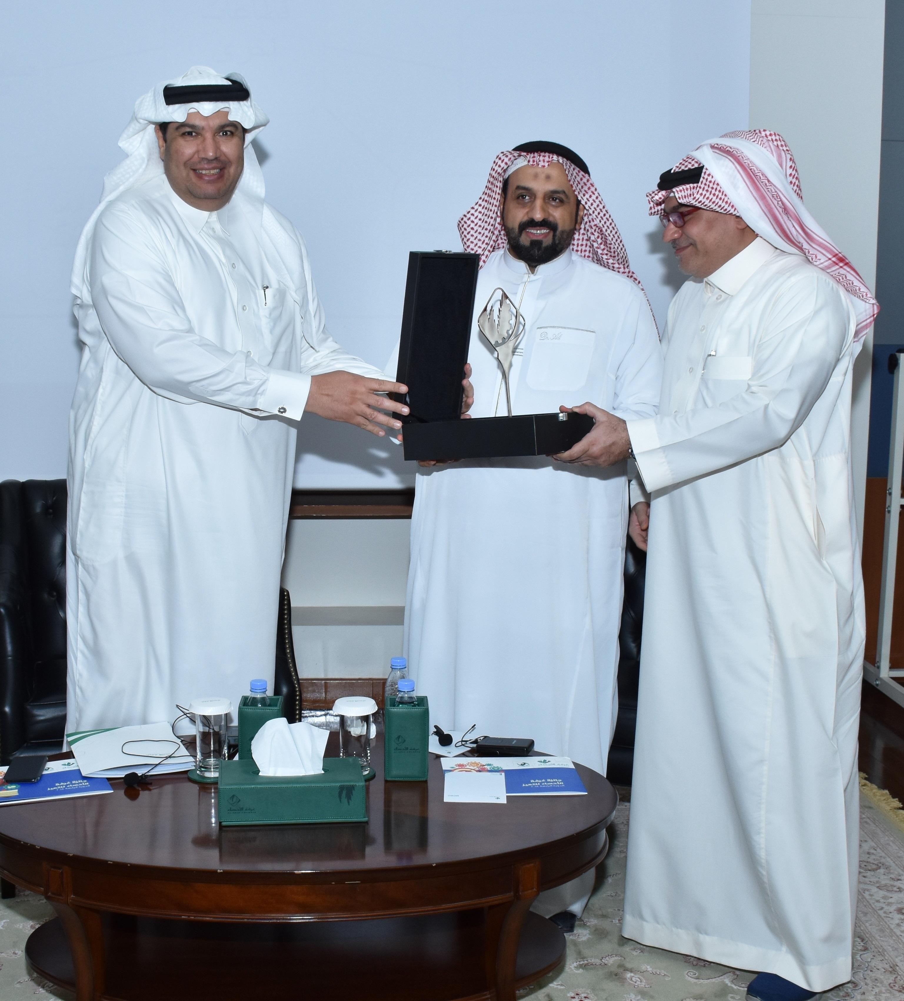 عضو مجلس الإدارة عماد الغدير يكرم المحاضر وبجانبه الطريفي رئيس اللجنة